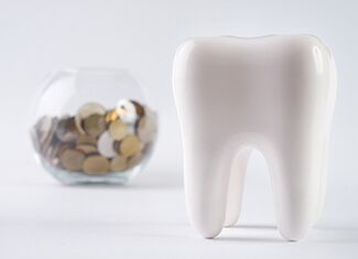 tooth next to a jar full of coins