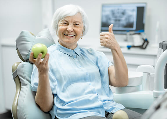 elderly woman giving a thumbs-up and holding a green apple