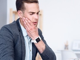 Man in need of T M J therapy holding jaw