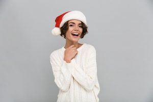 woman smiling and wearing Santa hat