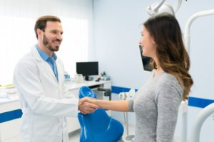 Dentist and patient shaking hands