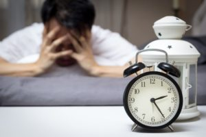 man tired head down by clock