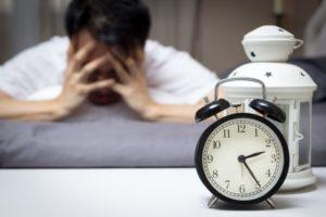 man tired head down by clock