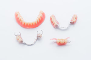 Full and partial dentures on white background