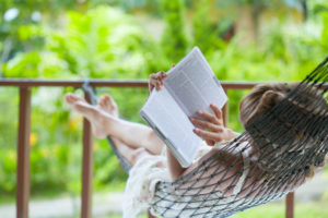 Woman lying in hammock in backyard, reading
